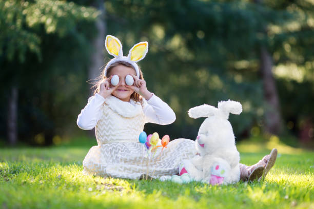 Little Caucasian girl in festive dress and bunny ears headband sitting on green grass and playing with Easter eggs and plush big bunny toy stock photo