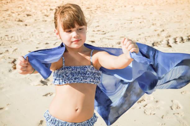 Menina pouco caucasiana joga com xale azul - foto de acervo
