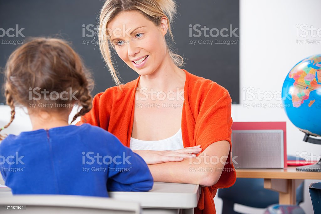 Little Caucasian Schoolgirl Interacting With Her Teacher stock photo