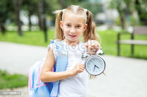 istock A little cheerful student with a clock. The concept of school, study, education, friendship, childhood. 1021688610