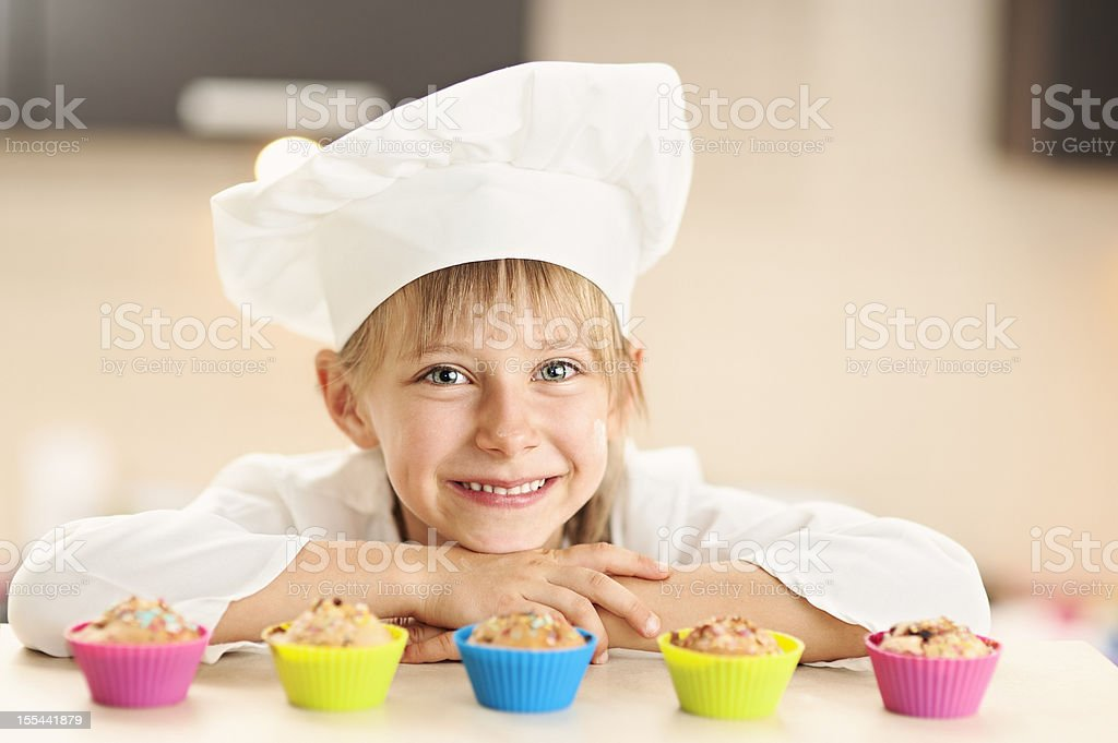 Little chef and her cupcakes stock photo