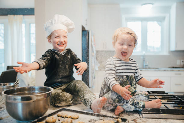 Little Chef Annoying his Baby Sister at the Kitchen stock photo