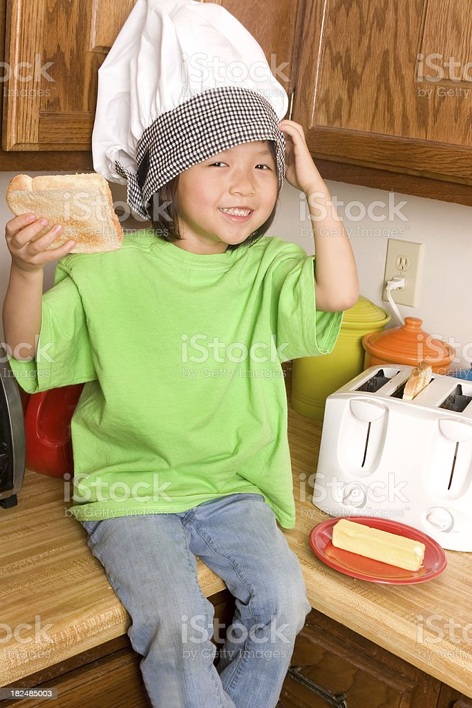 Little Chef holds up toast she made royalty-free stock photo