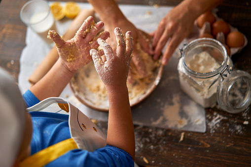 6-7 years old child and his mother are making a cake at kitchen together