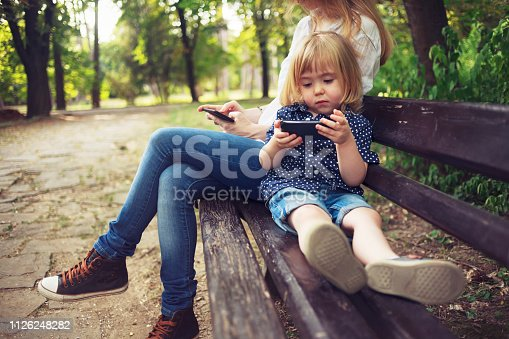 Bored little child and his mom using smart phones in a park. Digital native.