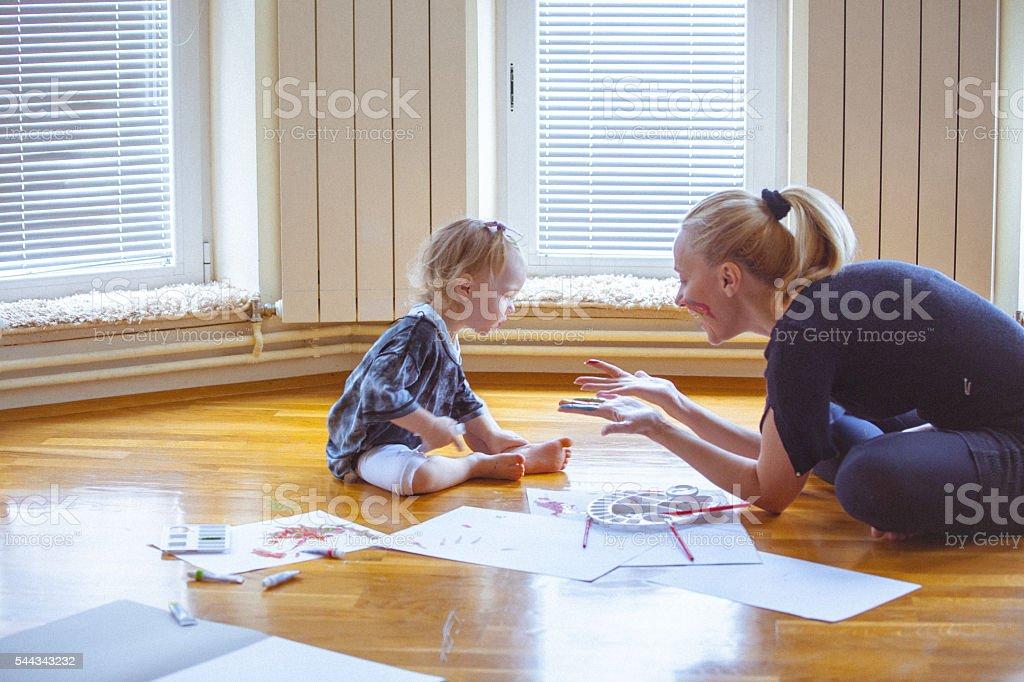 Pequeña hija y madre jugando con los colores y Pintando juntos - foto de stock