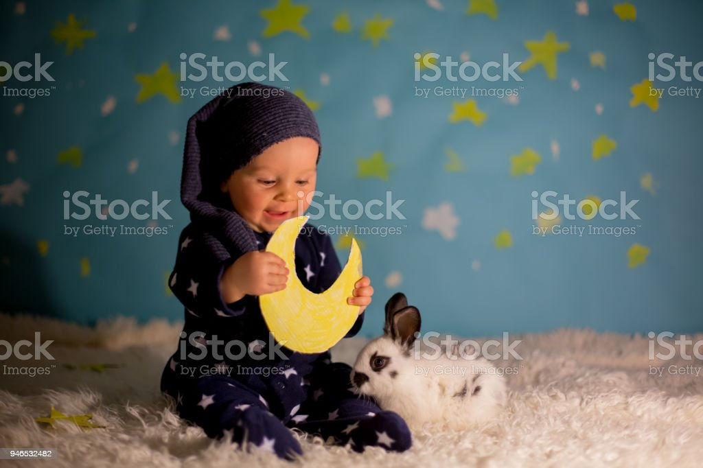 Little child, baby boy with cute white bunny and moon on a blue star and moon background stock photo