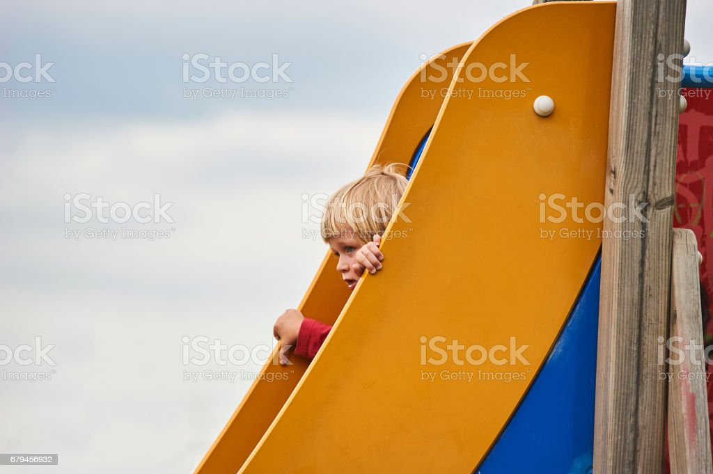 Little child blond boy sliding down a slide at the summer playground royalty-free stock photo