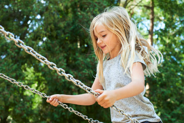 Little child blond girl having fun on a swing outdoor at summer. stock photo
