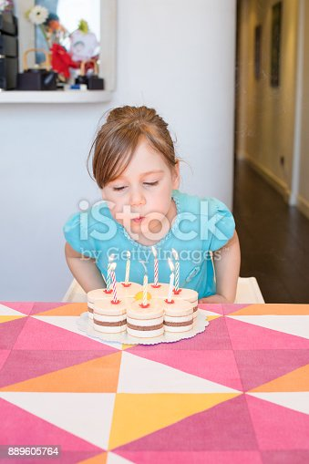 istock little child blowing burning candles on cake 889605764