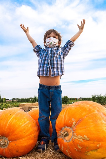 Caucasian Little child boy at a pumpkin patch wearing a protective face mask with his hands up looking at the sky