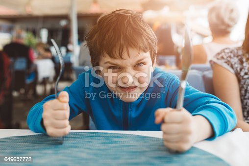 istock Little child boy hungry waiting for dinner in restaurant 649657772