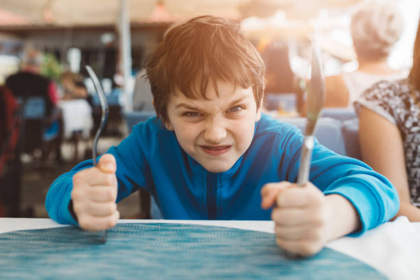 Little child boy hungry waiting for dinner in restaurant stock photo