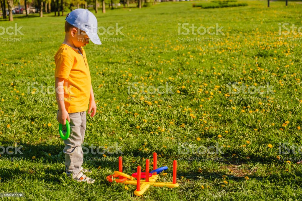 Little child boy playing. Ring throw summer game on a green lawn in...