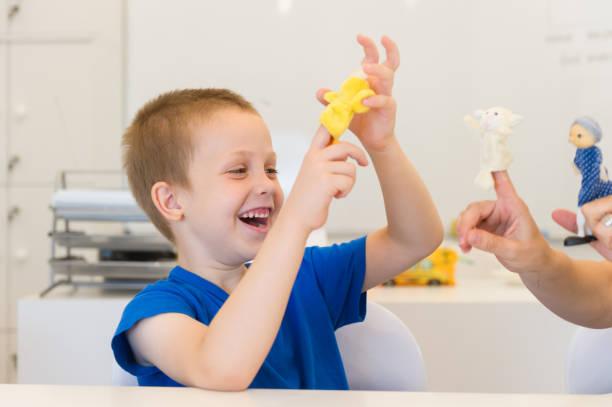 petit garçon enfant jouant avec la marionnette à doigt en salle de classe - Photo