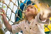 Cute little child climbing on the playground.