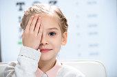 little child closing eye with eye test behind