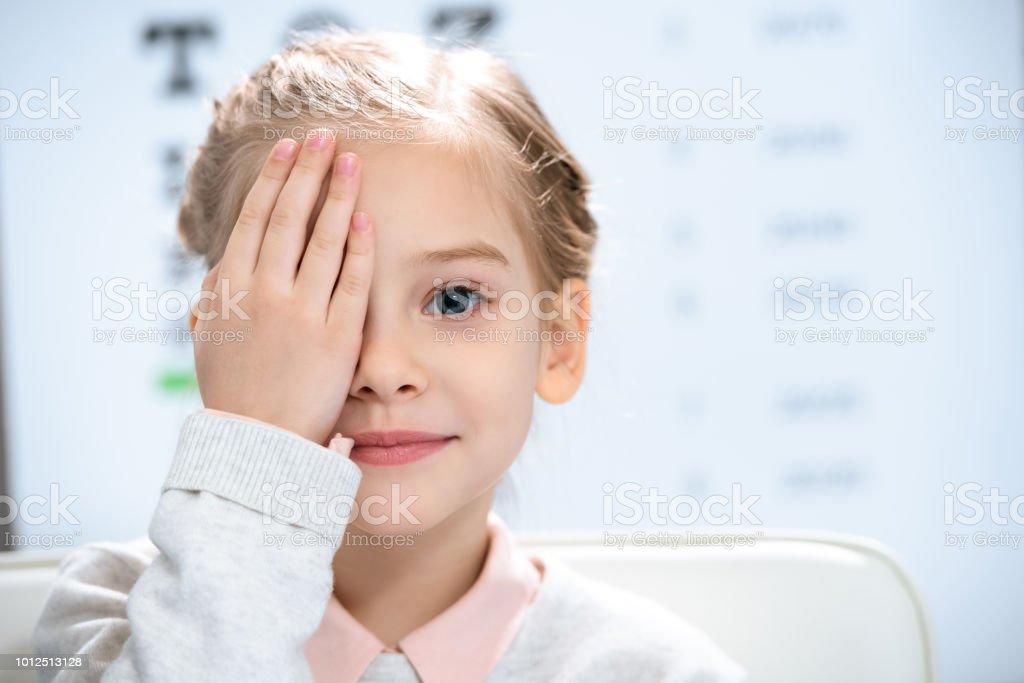 kleines Kind schließen Auge mit Sehtest hinter – Foto