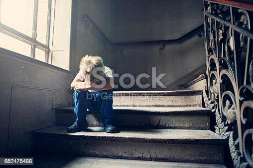 Depressed 6 years old child sitting on stairs in old staircase. The boy is crying and hiding his head in arms.