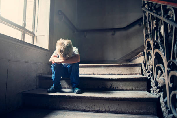 Little child crying on an old staircase stock photo