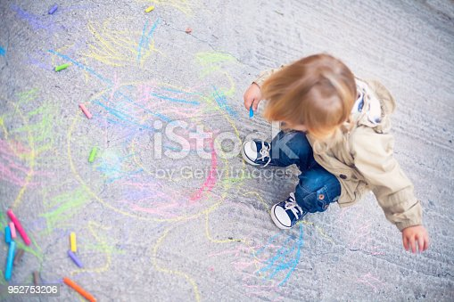 istock Little child drawing with sidewalk chalks 952753206