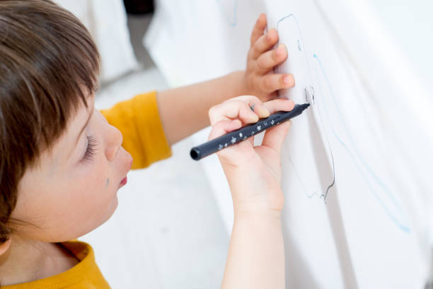 little child draws on a white board with a felt-tip pen. Home activities in self-isolation stock photo