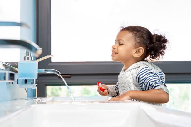 Little child girl brushing teeth in bathroom stock photo
