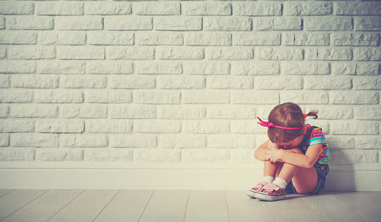 istock little child girl crying and sad about brick wall 506591102