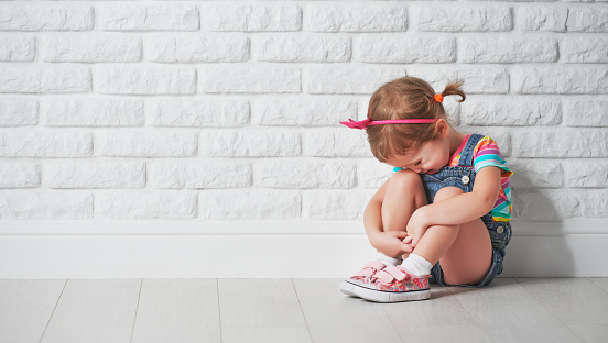 istock little child girl crying and sad about brick wall 507458304