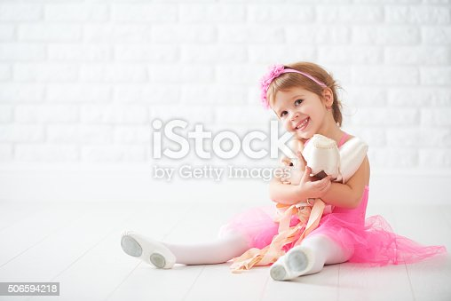 istock little child girl dreams of becoming  ballerina with ballet shoe 506594218