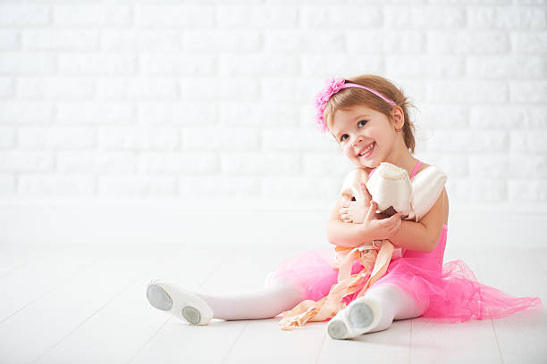 little child girl dreams of becoming  ballerina with ballet shoe stock photo