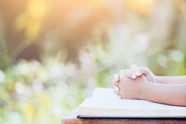 Kleines Kind Mädchen Hände gefaltet im Gebet auf eine Bibel – Foto