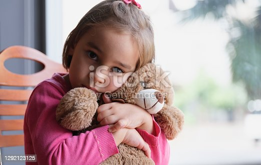 Little Child Girl Hugging Her Toy Bear At Home Nearby Window