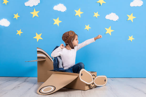 Little child girl in a pilot's costume is playing and dreaming of flying over the clouds stock photo
