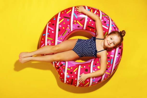 ett litet barn flicka i badkläder kostym ligger på en munk uppblåsbara cirkel. gul bakgrund. topp-vy. - inflatable ring bildbanksfoton och bilder