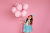 adorable smiling little child girl in blue dress and birthday hat with pastel pink air balloons thinking about something on pink background. birthday party.