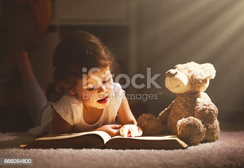 istock Little child girl is reading a book in evening in dark with a toy bear 666064800