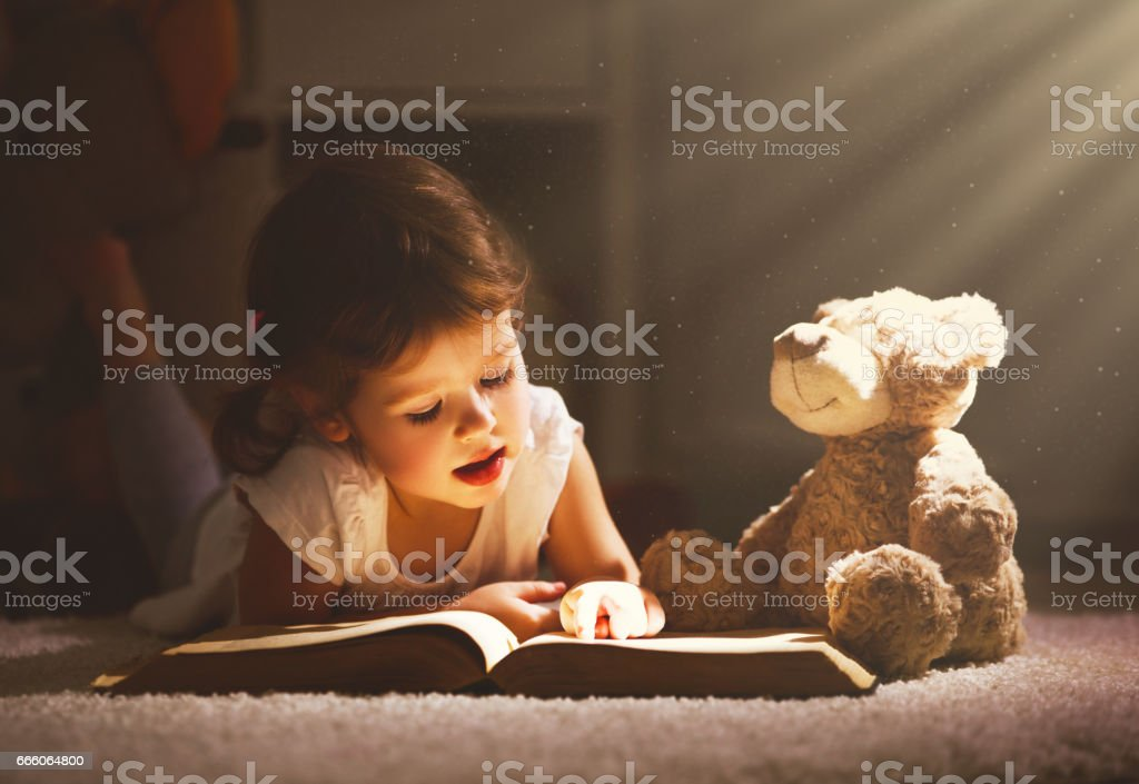 Little child girl is reading a book in evening in dark with a toy bear stock photo