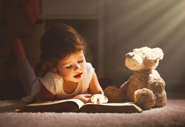 petite fille enfant lit un livre soir dans l'obscurité avec un ours jouet - doudou photos et images de collection