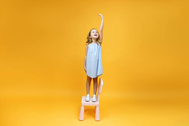 a little child girl is standing on a chair and measuring her he - bassino foto e immagini stock