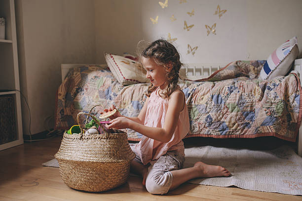 little child girl playing in her room with toy food stock photo