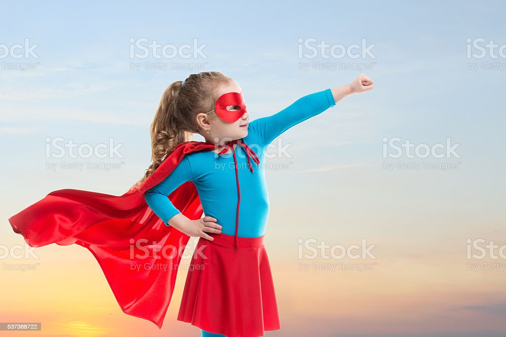 Little child girl plays superhero. stock photo