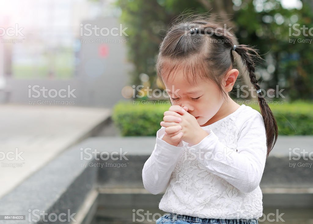Little child girl praying in the garden. royalty-free stock photo