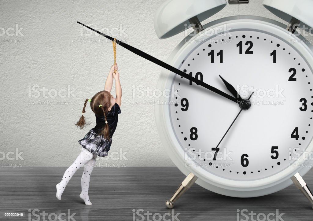Little child girl pulling hand clock, time management concept stock photo