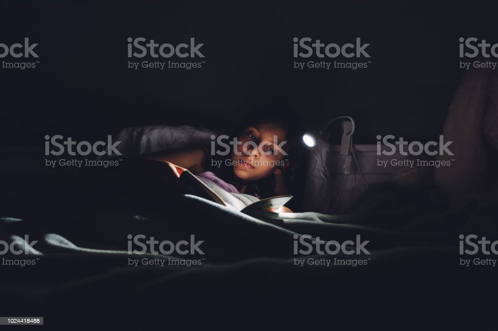 Little child girl reading a digital book at bedtime stock photo