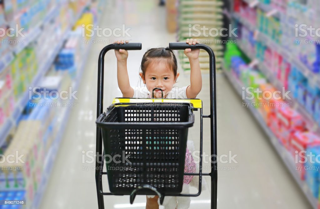 Little child girl shopping at the supermarket. stock photo