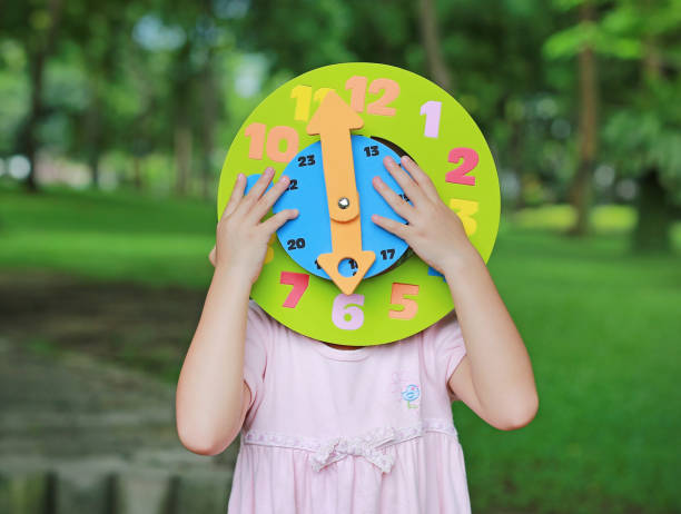 Little child girl showing up 6 O'clock round toy clock in the garden. stock photo