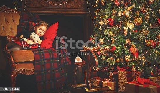 istock little child girl sleeping near a Christmas tree 616131996