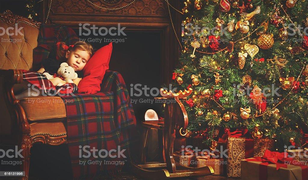little child girl sleeping near a Christmas tree - foto stock