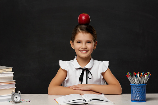 little child girl studying in classroom on background of blackboard. schoolgirl with red apple on her head. Back to school.